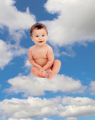 Little baby sitting on cloud in sky — Stock Photo