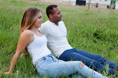 Couple lying on the grass in the field — Stock Photo