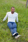 Handsome guy sitting on the grass — Stock Photo