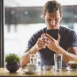 Young man watching tablet in cafe — Stock Photo #54173375