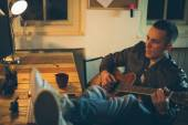 Man playing guitar at home after work — Stock Photo