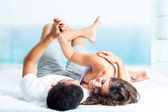 Young couple showing affection in bedroom . — Stock Photo