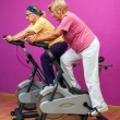 Two golden agers doing spinning in gym. — Foto Stock