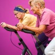 Senior women doing spinning in gym — Stockfoto