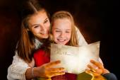 Girl reading Christmas card to sister. — Stockfoto
