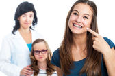 Teen girl pointing at dental barces with doctor in background. — Stock Photo