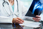 Medical practitioner writing down prescription. — Stock Photo