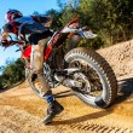 Постер, плакат: Motocross bike taking off on dirt road