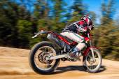 Teen boy riding Motocross bike on gravel road — Stock Photo