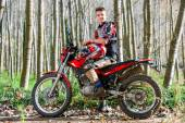Handsome teen boy sitting on motocross motorbike. — Stock Photo