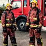 Firemen standing next to fire truck. — Stock Photo #62185803