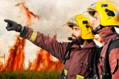 Firemen indicating fire to companion. — Stock Photo