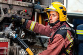 Fireman controlling water pressure at truck. — Stock Photo