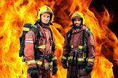 Firemen against burning background. — Stock Photo