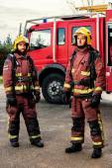 Firemen standing next to fire truck. — Stock Photo