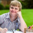 Boy with down syndrome at desk holding glasses. — Stock Photo #62329837