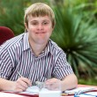 Boy with down syndrome at desk outdoors. — Stock Photo #62329871