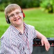Boy with down syndrome wearing headphones. — Stock Photo #62329893