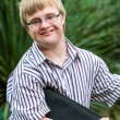 Young student with down syndrome holding files outdoors. — Stock Photo #62329913