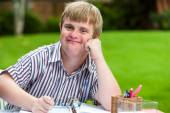 Boy with down syndrome at desk holding glasses. — Стоковое фото