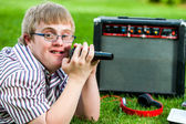 Handicapped boy singing with microphone and amplifier. — Stockfoto