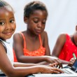 Little African girl doing homework on computer with friends. — Stock Photo #63454493