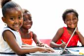 Threesome African kids with laptop at table. — Stock Photo