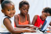 Little African girl doing homework on computer with friends. — Stock Photo