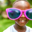 African boy wearing fun extra large sun glasses. — Stock Photo #64619597