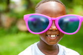 African boy wearing fun extra large sun glasses. — Stock Photo