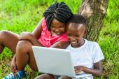 African boy and girl playing on laptop. — Stock Photo