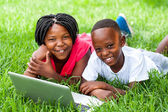 Two african kids laying on grass with laptop. — Stock Photo