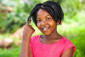 Cute African girl showing braided hair. — Stockfoto