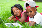African kids laying on grass with laptop. — Stock Photo