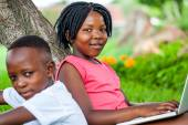Cute african girl typing on laptop next to brother. — Stock Photo