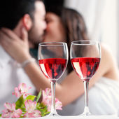 Wine glasses with couple kissing in background. — Stock Photo