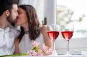 Detail of wine glasses with couple in background. — Stock Photo