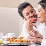 Couple in bathrobe having fun eating fruit. — Stock Photo #70260477