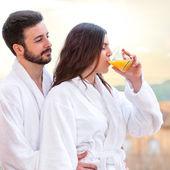 Couple in bathrobe drinking fruit juice. — Stock Photo