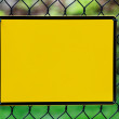 Blank yellow info plate hung on a fence — Stock Photo #52108479