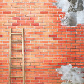 Red brick wall with wooden ladder — Stock Photo