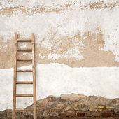 Stucco wall with wooden ladder — Stock Photo