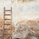 Weathered stucco wall with wooden ladder — Stock Photo