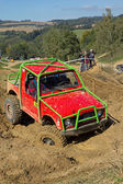 Red off road car in the deep mud. Vertically. — Stockfoto