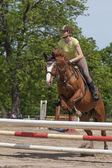 Horsewoman is jumping. Vertically. — Stock Photo