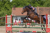 Closeup of young horsewoman jumping. Horizontally. — Stock Photo