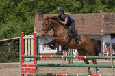Young horsewoman in black is jumping a brown horse — Stock Photo