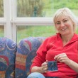 Smiling blonde middle-aged woman is relaxing on a sofa — Stock Photo #73394315