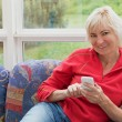Blonde middle-aged woman is holding a cell phone — Stock Photo #73394341