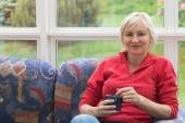 Blonde middle-aged woman is sitting on a sofa — Stock Photo